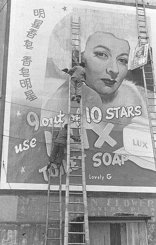 A worker putting up a billboard for Lux Soap in the late 1940's.