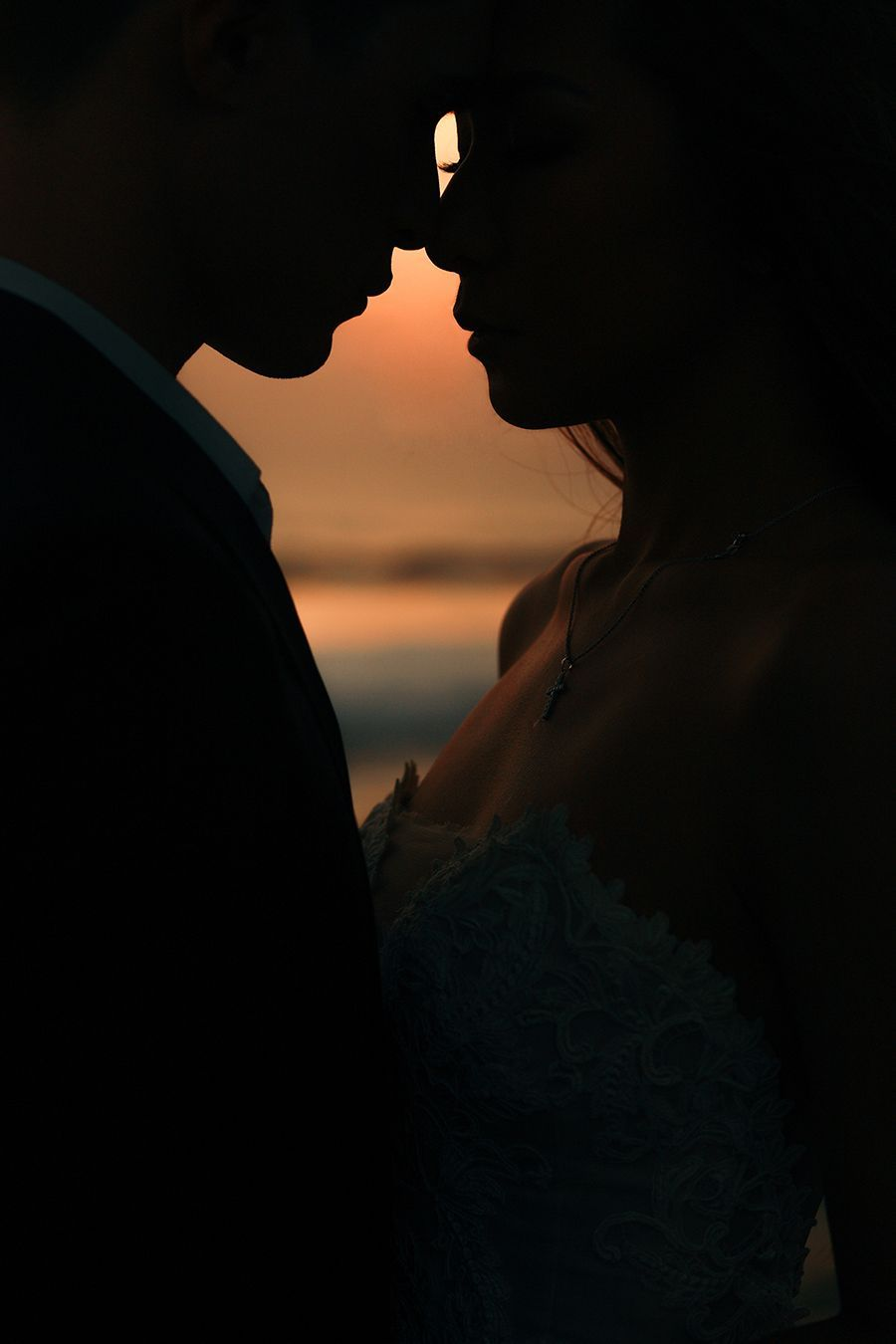 cd878f2a4e3a Engaged couple touching foreheads with their silhouettes outlining a glimpse  of the sea    Following