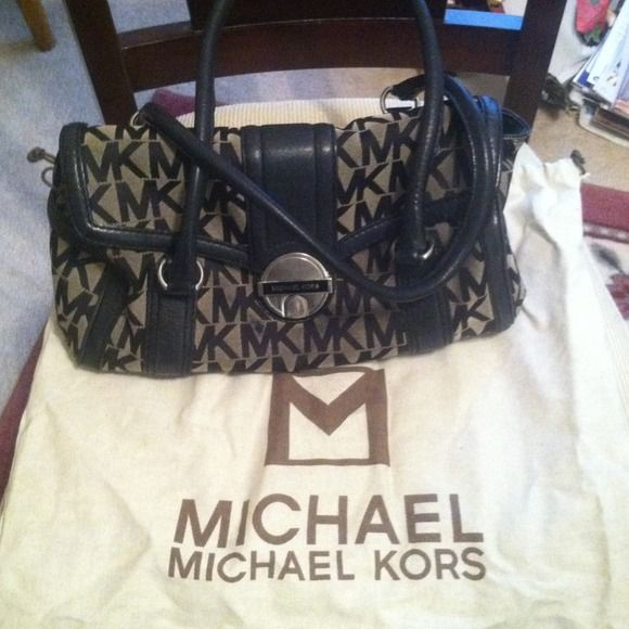 Michael Kors Handbag Monogram Michael Kors canvas handbag with a buckle closure. Little bit of natural wear, but in great condition. Small stain on the inside of the bag, but could be cleaned. Slight scratches on the buckle. Comes with original dust bag. Michael Kors Bags