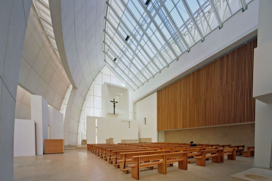 Inside, a cool, modern austerity prevails, with simple wood pews and a stone floor, altar, and priest's chairs. The building, which was completed in 2003, also has a number of cleverly concealed green features—a titanium dioxide coating makes the exterior self-cleaning and capable of scrubbing pollution, and the large thermal mass of the concrete walls balances temperature throughout the day.