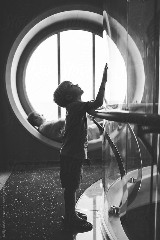 curious child watches a glass elevator by Kelly Knox #stocksy #realstock