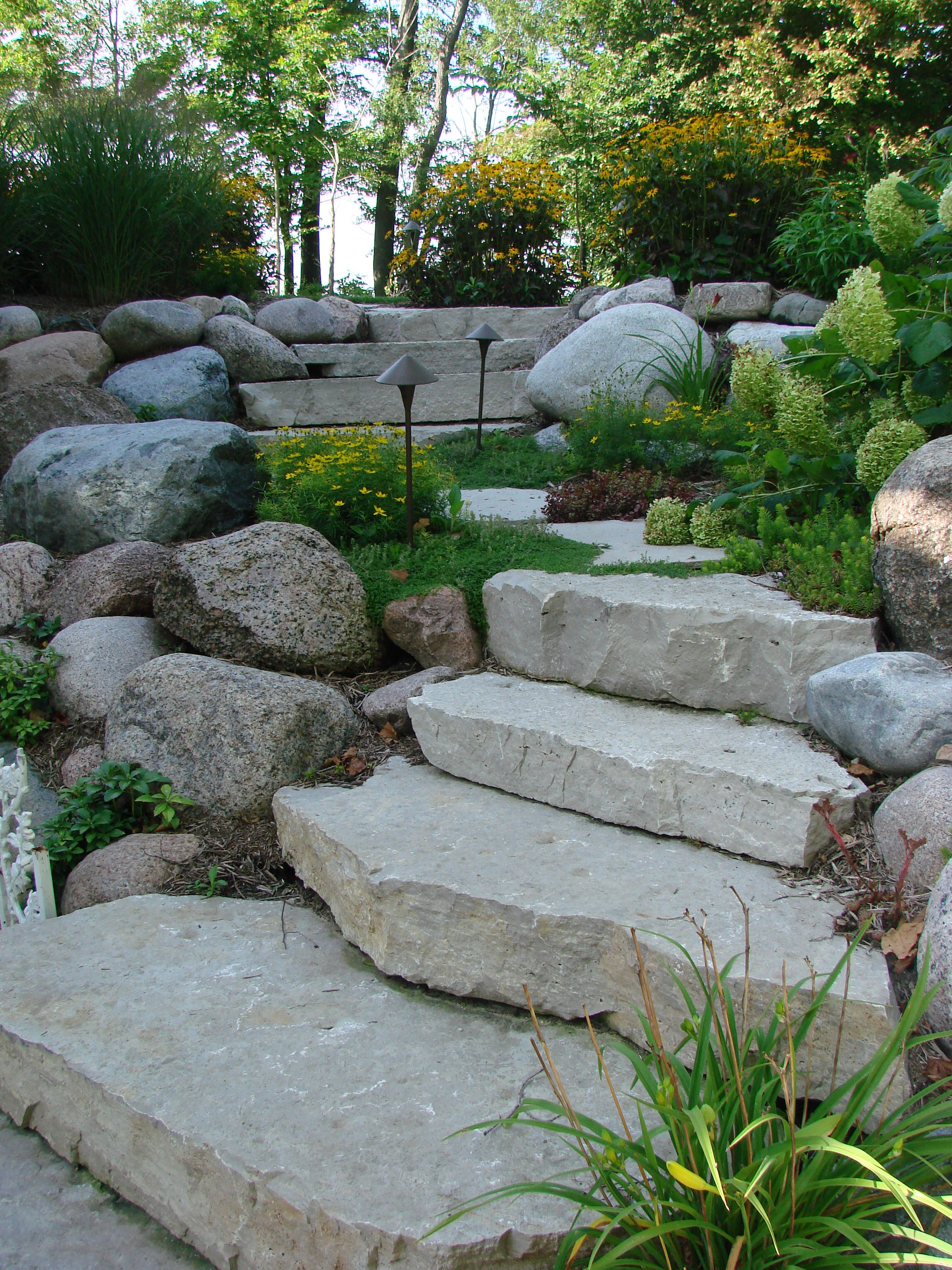 The natural stone steps of a stairway garden feature climb a small - Angled Steps Leading To And From The Patio