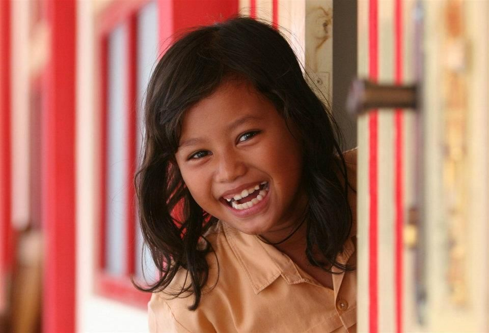 A girl smiles outside a classroom door at a primary school in Bantul District, Indonesia.