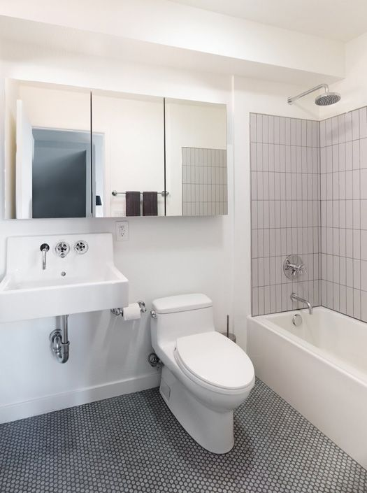 Economical Bathroom Using Penny Round Tiles In The Shower Area