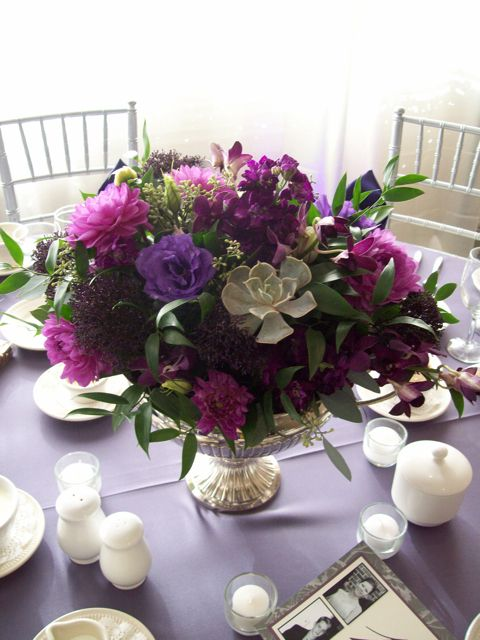 Purple guest table centerpiece in silver grecian urn vase