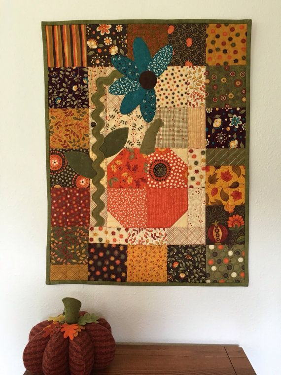 This whimsical seasonal wall hanging features a turquoise flower with ric rac stem and an orange pumpkin. Background is quilted with decorative stitching and machine blanket stitch finishes the appliqué. Majority of fabric is from collections by Sandy Gervias. The hanging has a narrow sleeve for ease of hanging. 22.5 x 29