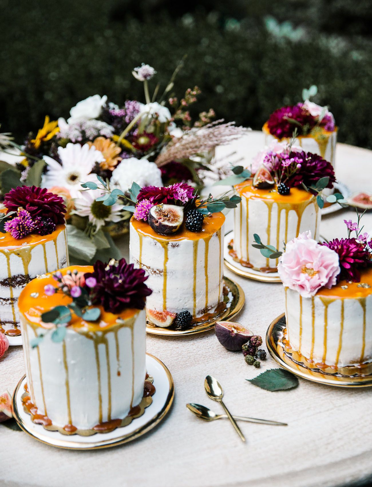 Individual cakes for the sweetheart table plated on gorgeous gold gilded plates from BHLDN. Fall florals atop dripping caramel and flakes of gold make for some stunning treats.