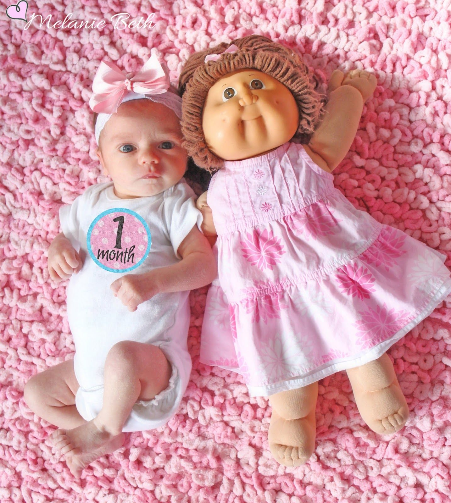 Monthly pics next to the same doll to compare baby's growth