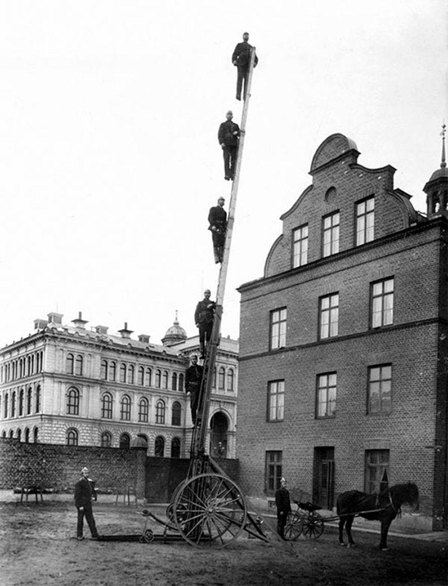 Pompiers suédois posant sur une échelle, vers 1900.