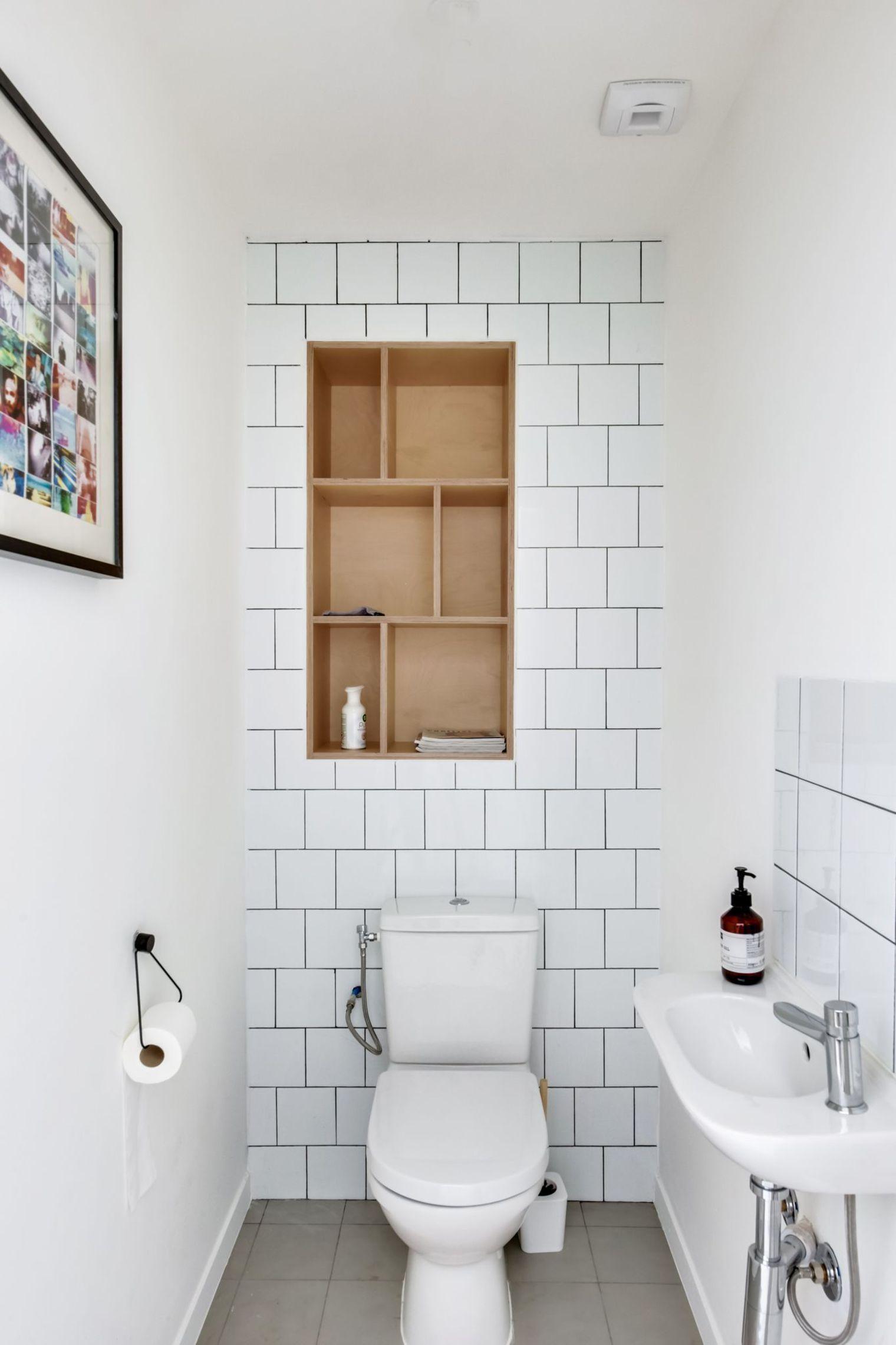 Une niche en bois bien pratique dans ces toilettes blanches ...