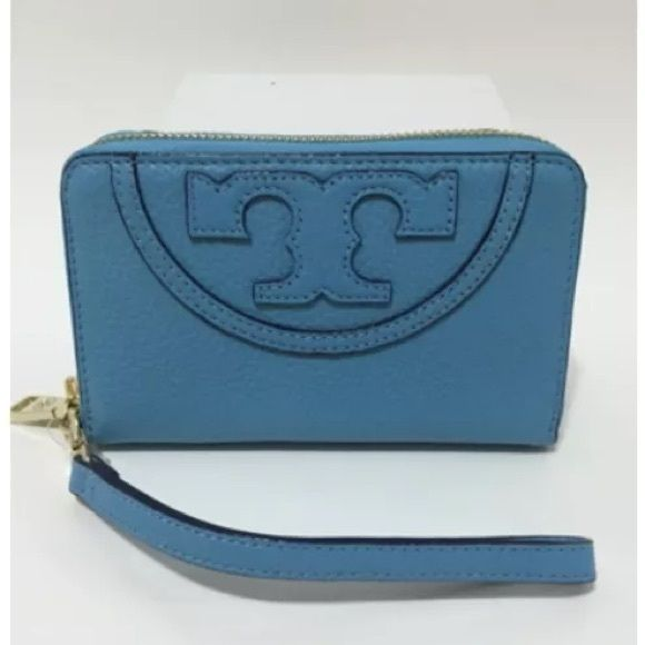 """Tory Burch All-T Smartphone Wristlet Tory Burch All-T Smartphone Wristlet 100% Authentic  Color: Juniper Berry / 409, Blue Style: 21159475 Retail: $155.00  With the ability to function as a streamlined wallet or a clutch, this logo-topped Tory Burch wristlet houses your iPhone 5/5s or iPhone 6 alongside essential cards, cash and keys. Wristlet strap Zip closure; lined Fits iPhone 5/5s and iPhone 6 pocket 6""""L x 1""""W x 4""""H Leather Imported Tory Burch Bags Clutches & Wristlets"""
