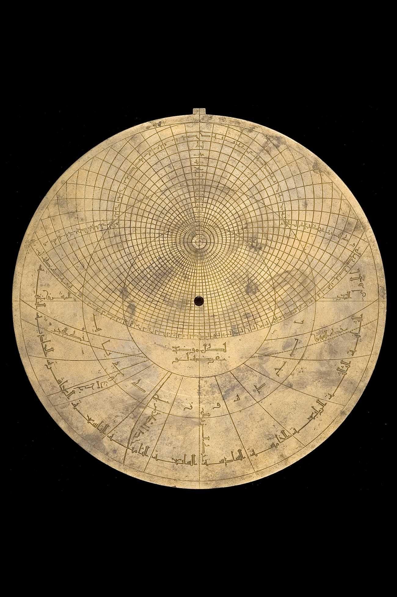 Date: 1221/2. Maker: Muḥammad ibn Fattūḥ al-Khamā'irī. Place: Seville. Material:Brass. Astrolabe Catalogue Inventory no.44141. The throne is of the moorish arch type made of brass attached with integrated base made of brass and omega type shackle made of brass . The rete contains 29 stars. The zodiac on the rete is labelled: الحمل , الثور , الجوزا , السرطان , الاسد , السنبله , الميزان , العقرب , القوس , الجدي , الدلو , الحوت.