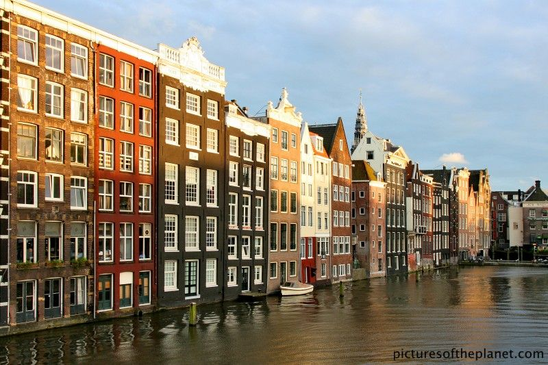 Evening photograph of traditional looking Amsterdam apartments and houses lining the side of a man made canal.