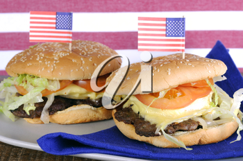 Happy Fourth of July, USA celebration party food, hamburgers wtih Stars and Stripes flags against red and white stripe background and natural recycled wood table.