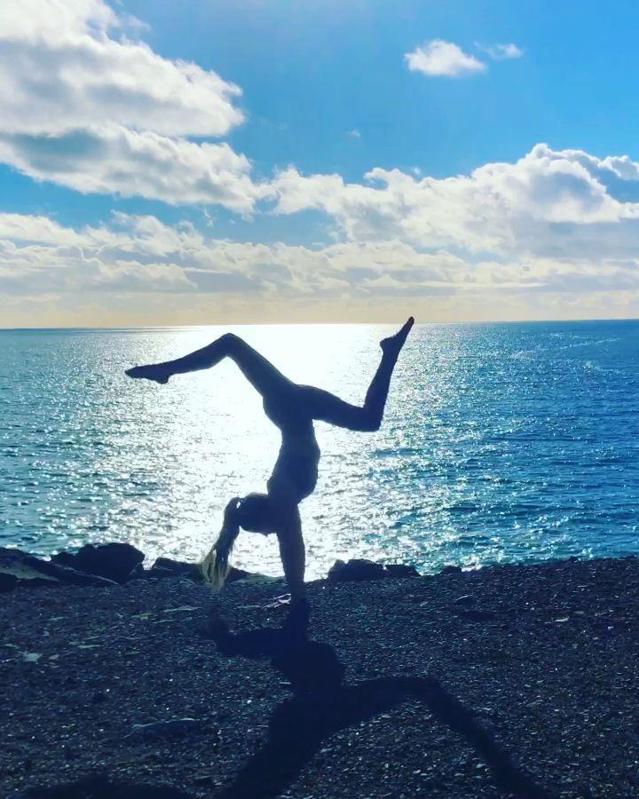 Practicing yoga on a beach cliff. #handstand #fitness #sunset #inspirational #interiordesignideasona...