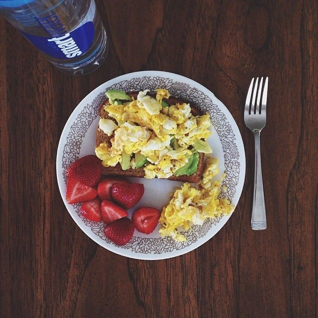 Multigrain toast with 1/2 an avocado, scrambled eggs with cheese, topped with cracked black pepper and pink Himalayan salt and a side of sliced strawberries.