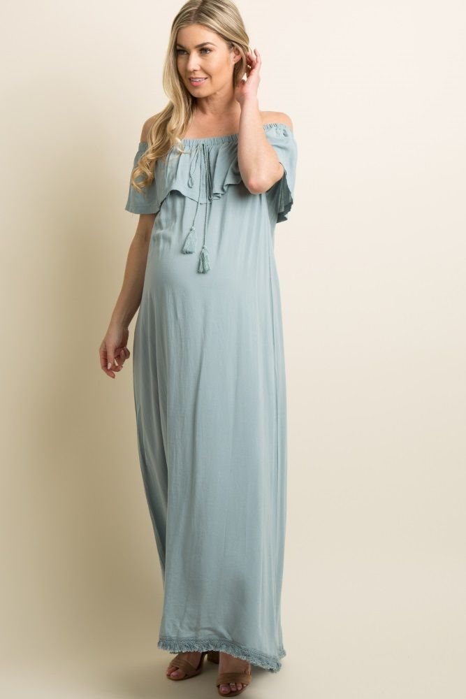 cc5e601b872 A solid hued linen maternity maxi dress featuring a cinched off shoulder  neckline with a slit front ruffle trim and a twisted tassel tie accent.