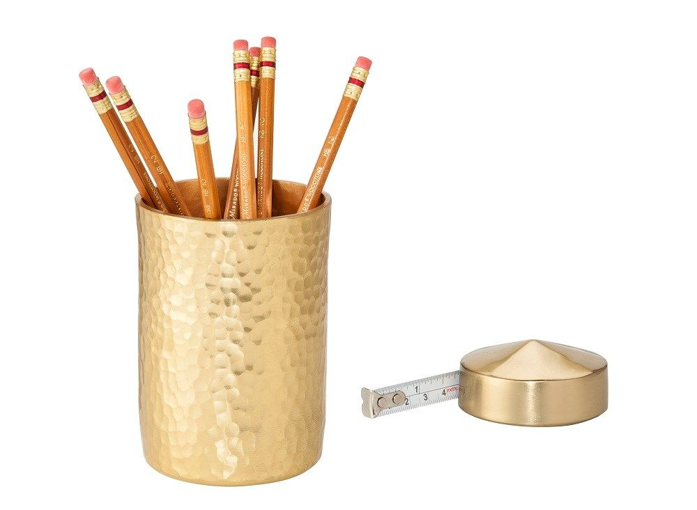 a gold textured pencil cup with pencils and gold tape measure from