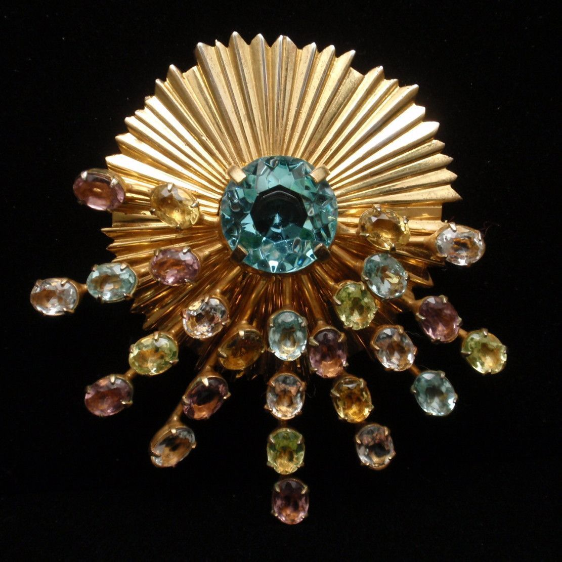 Lovely brooch in gold tone metal and multi-colored rhinestones. The base has a fluted design and is adorned with spikes or a starburst of multi-colored pastel stones. The overall look is very eye-catc
