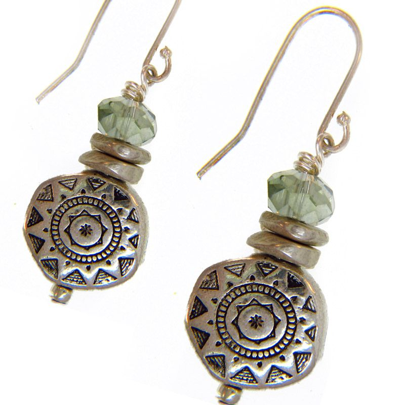 Featuring a unique etched sunburst design on silver discs, these earrings are topped with faceted sea green crystals accented with silver wafers. Crafted with sterling silver, these handmade earrings hang from hook findings.