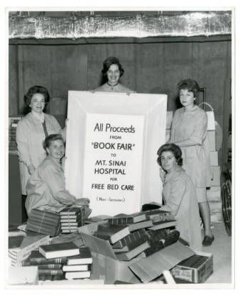 Volunteers from the Mount Sinai Hospital Women's Auxiliary display Book Fair sign while sorting books,   http://www.jhsum.org/