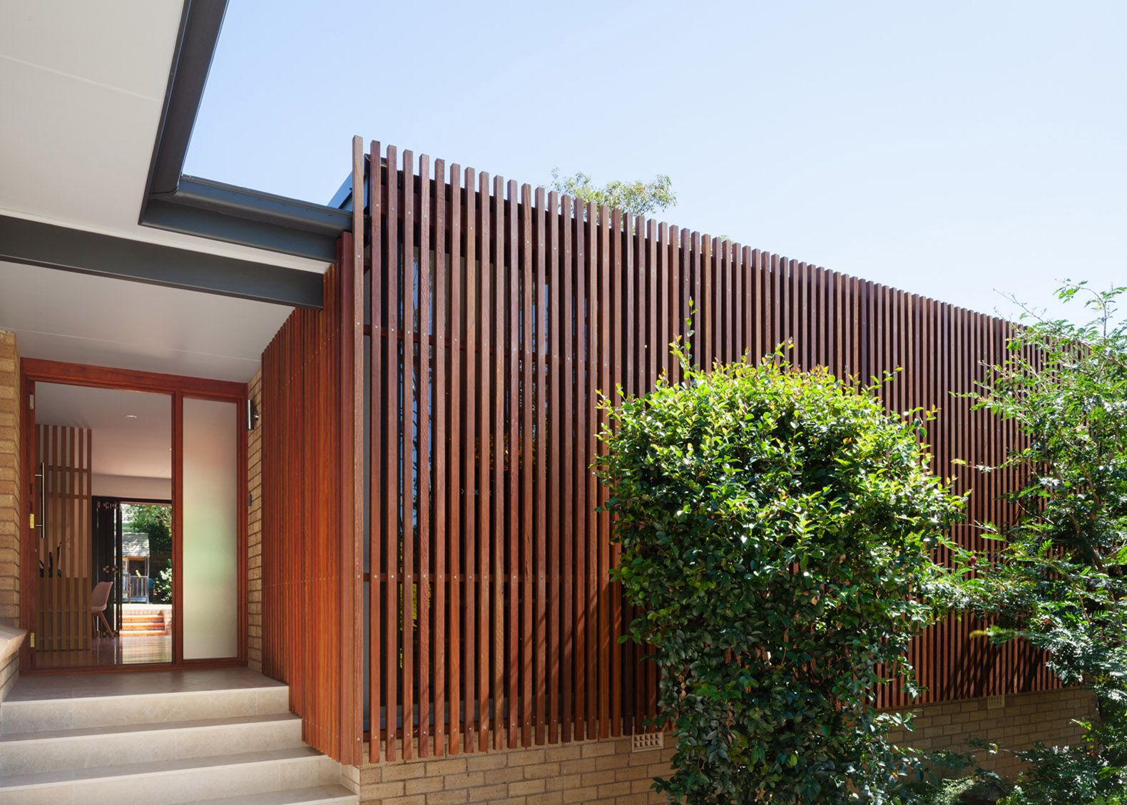 mid-century bungalow in sydney is wrapped in a stunning slatted