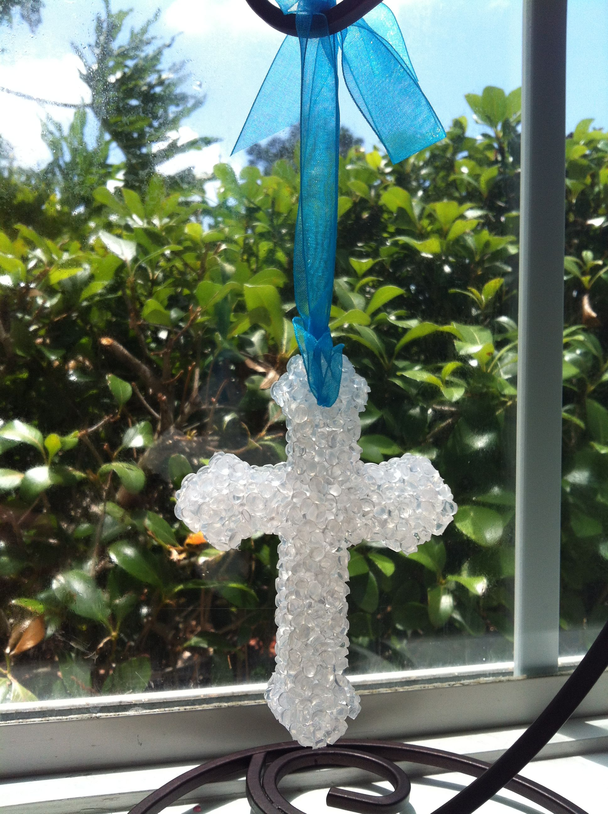 White cross aroma bead air freshener with teal ribbon