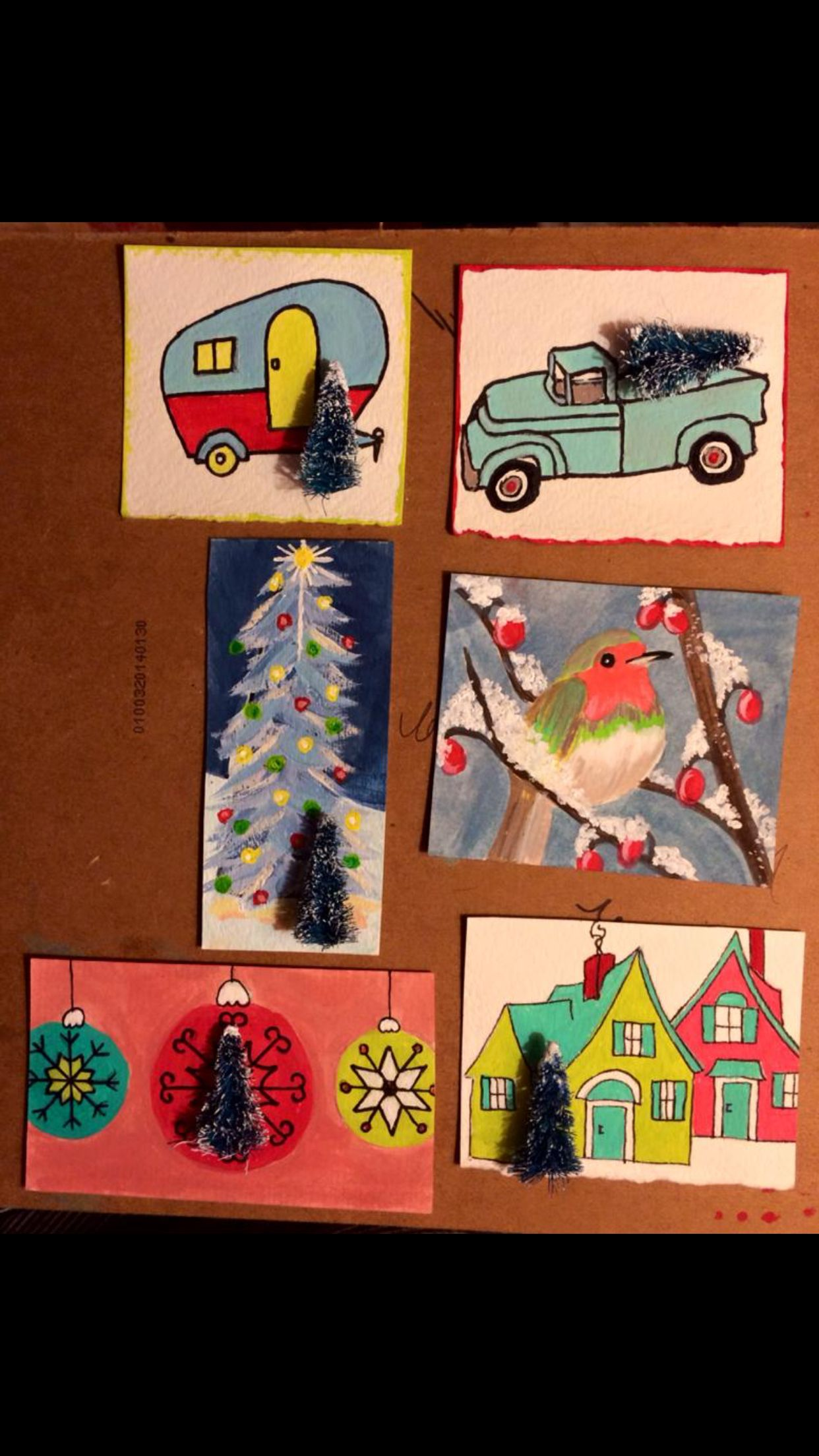 Hand painted ornaments on 140 watercolor paper. Small bottle brush trees attached. Made by Cont