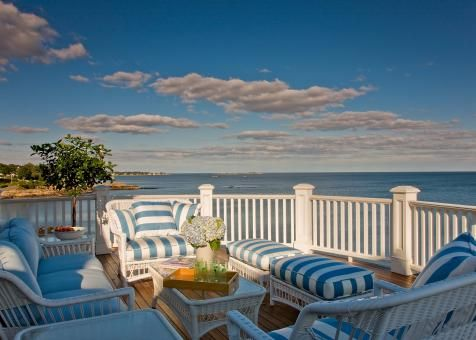 Take in the breathtaking ocean views on this coastal deck. White wicker chairs and benches, a glass-top coffee table and miles of ocean view make it a great place to entertain or just relax with family.