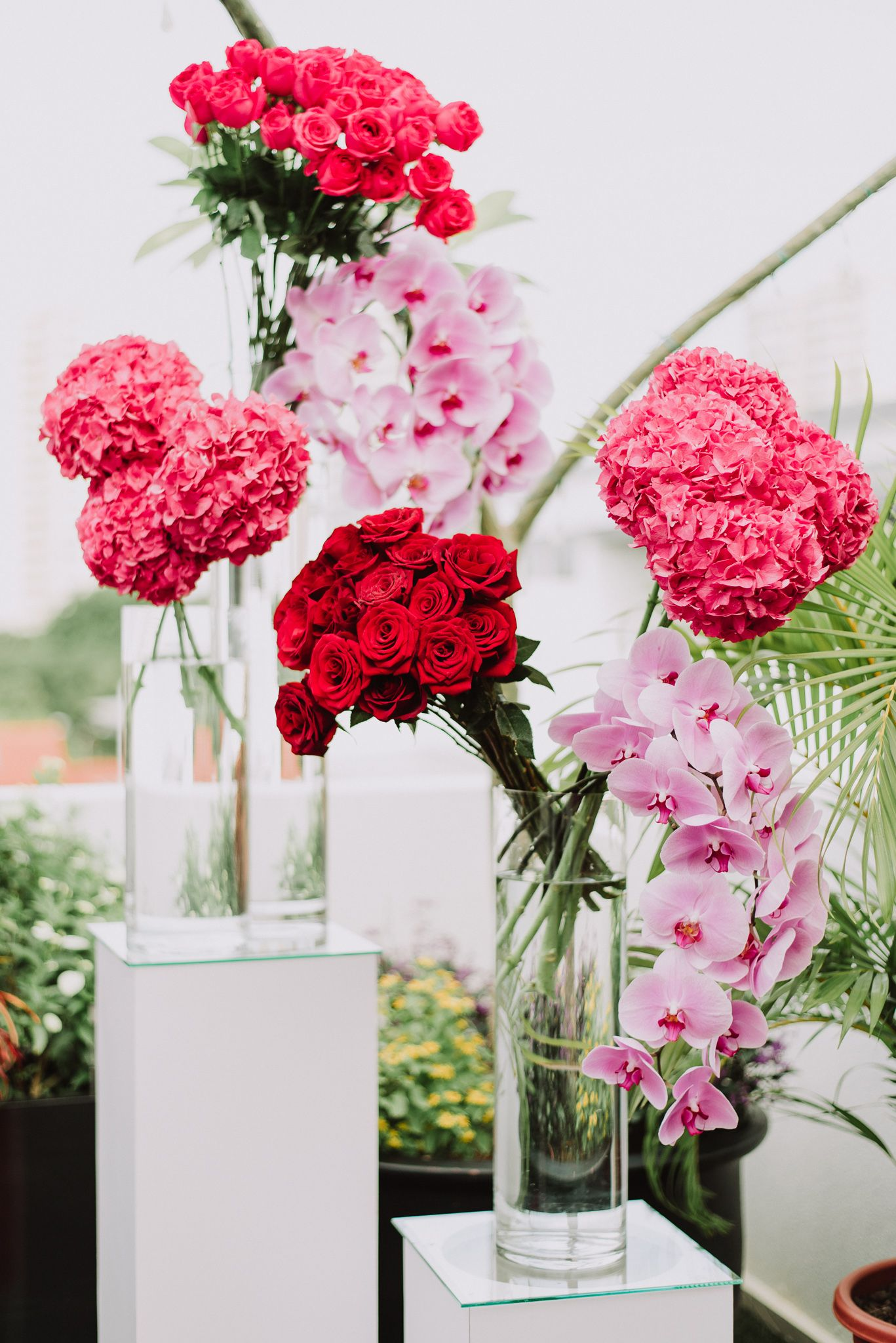 Wedding decor in shades of red pink and purple flower wedding decor in shades of red pink and purple flower arrangements in tall clear vases wedding planning chere weddings izmirmasajfo