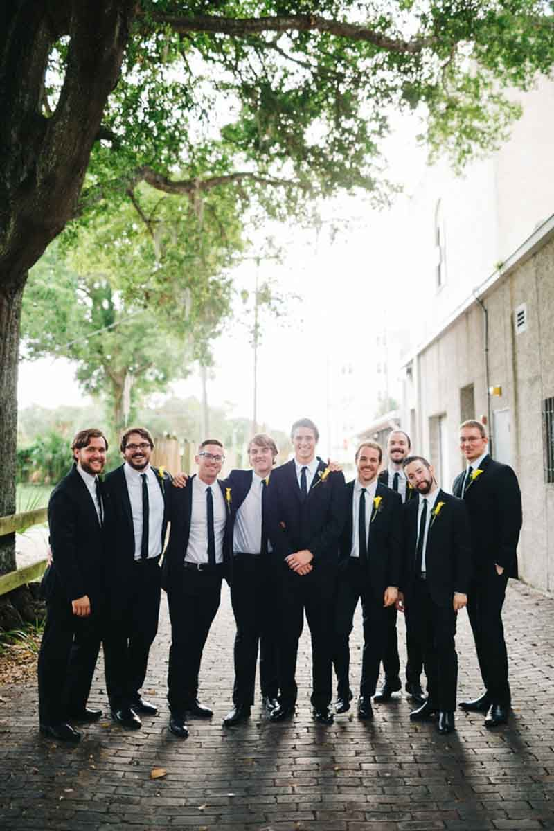 Groomsmen in black suits pink and yellow bridal bouquet by