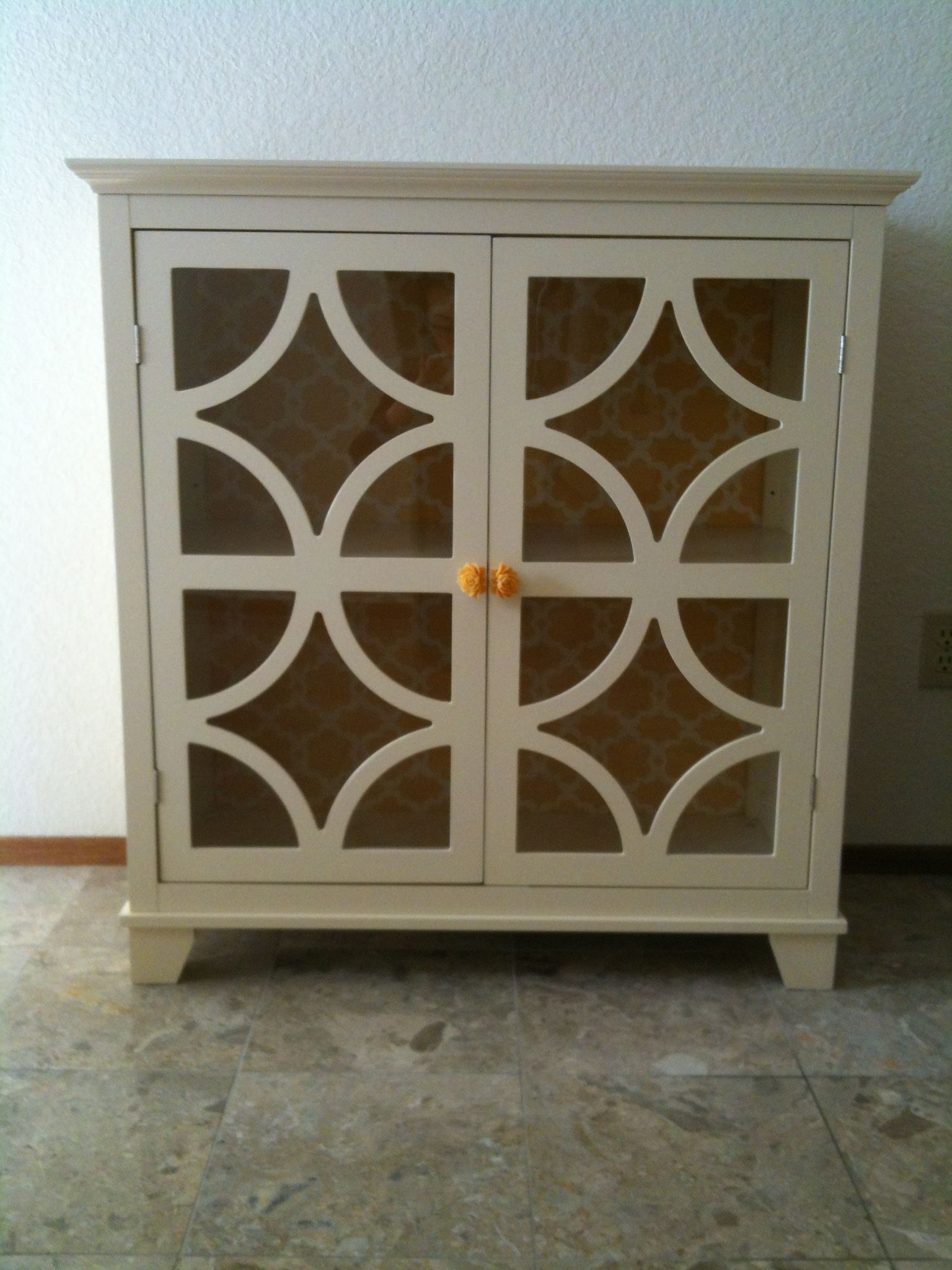 Dressed up a plain cabinet with new knobs and fancy fabric inside.