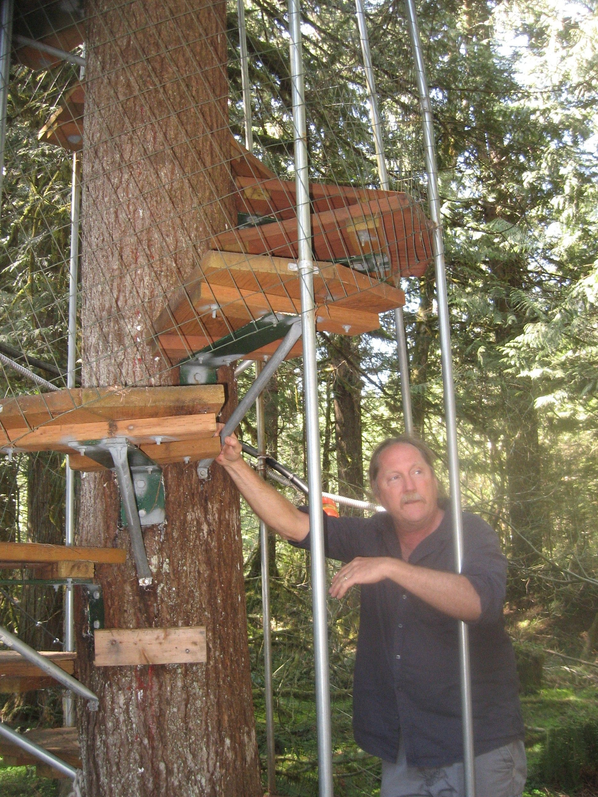 Circular Tree House cedar-creek-treehouse-bill-stnading-next-to-the-spiral-staircase