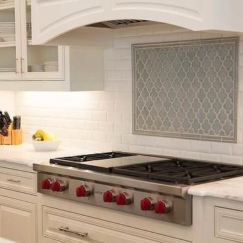an wolf integrated gas cooktop positioned against marble arabesque backsplash tiles between white shaker cabinets topped with a gray and white quartzite - Arabesque Tile Backsplash