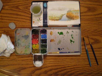 picture of one of tiny travel kits, this one is set up with a homemade 'Altoids' watercolor kit. Small watercolor brushes that were cut the handles off so they fit. The watercolor kit or box is stuck into a metal pencil case used to mix colors and hold paper and watercup.  Mary McAndrew .com