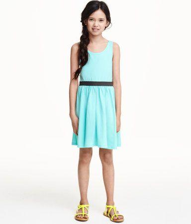071cc7db0312 En ärmlös klänning i trikå. Klänningen är avskuren med synlig resår i  midjan och har lätt utställd kjol.