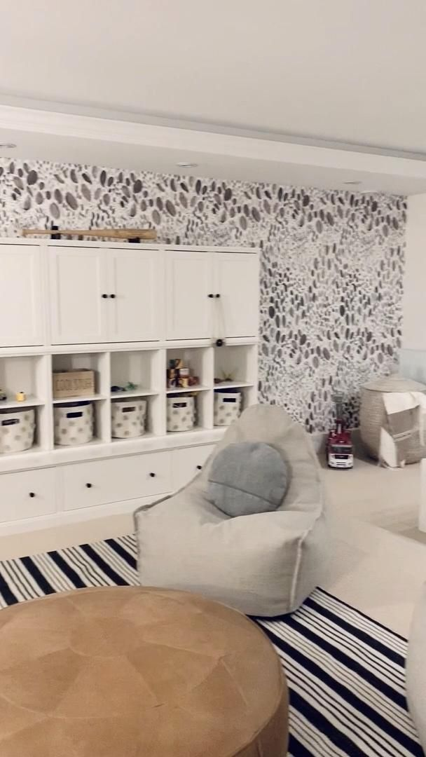 A bright media room turned kid's playroom complete with storage, bold wallpaper, TV lounge and snack bar!