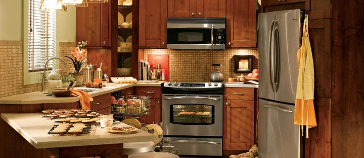 Small Kitchen GE Profile Kitchen with shaker style cabinets, tile backsplash and tile walls.