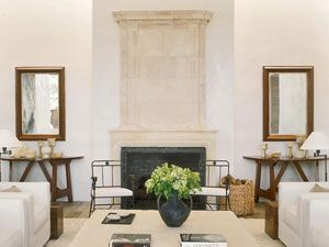 Atelier AM: Italian 18th-century consoles flank the Louis XIV fireplace. Bronze chairs by Diego Giacometti and seats in antique linen add layers of texture to the clean design.