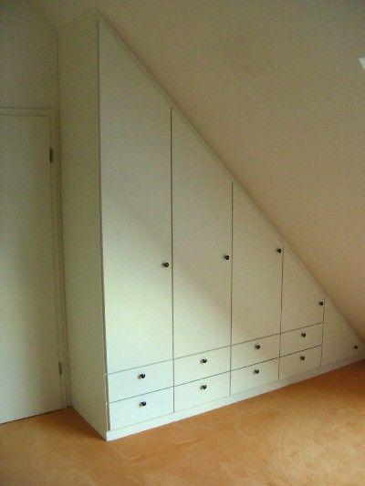 Weißer Dachschrägenschrank Mit Drehtüren Und Schubladen.
