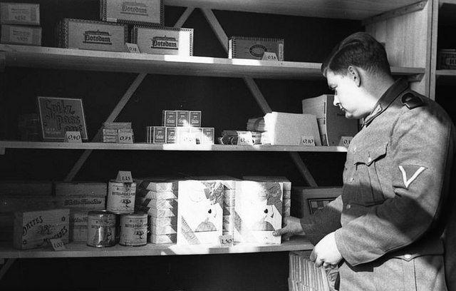 1943, France, Le fourrier allemand d'une caserne devant une étagère de produits proposés à la vente
