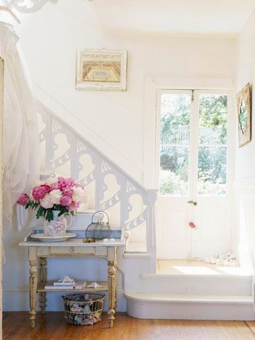 A French Flea-Market Retreat:   See how these homeowners blend the romance of France with chic cottage flair in their San Francisco Victorian. Original Details:   Gingerbread railings and classic French doors greet guests in this pretty foyer. To add a personal touch the homeowner hung her wedding dress as a piece of art above the small French table.