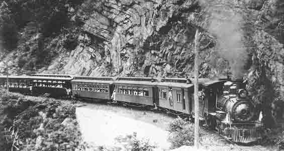 In the early 1880s the East Tennessee and Western North Carolina Railroad (ET) built their narrow gauge line from Johnson City, TN through the mountains to reach a source of high-grade iron ore in Cranberry, NC. The Doe River Gorge provided passage through the first range but not without serious challenge.
