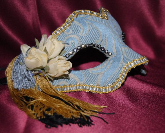 Beatiful mask elaborated in paper maché covered with elegant fabric damask,surrounded by golden trimmings and a bouquet of flowers and fringed in