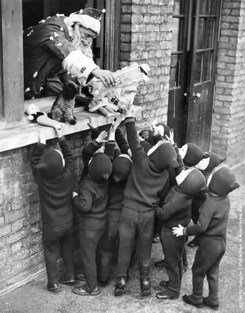 Father Christmas hands out presents to children at the Aid And Adoption Society home at Leytonstone. (Photo by Gerry Cranham/Fox Photos/Getty Images). 7th December 1938