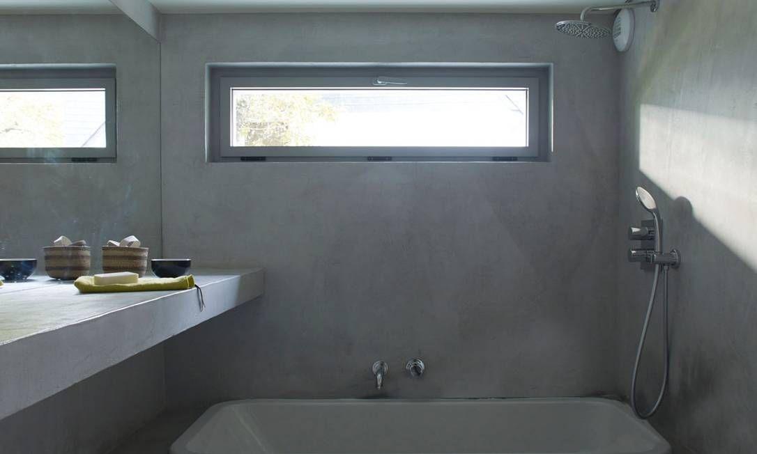 Banheiro minimalista e com linhas retas, presentes na bancada, contorno da banheira e janela.