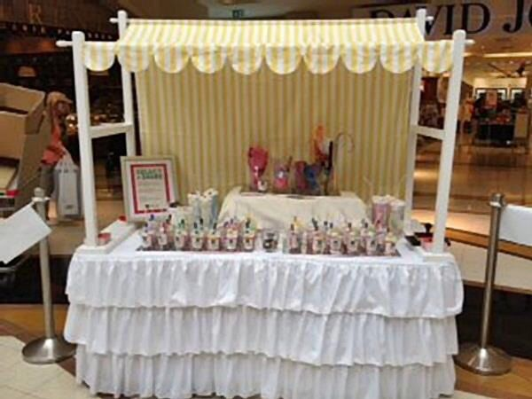Yellow Striped Canopy And Frame Sit Upon White Ruffled Tablecloth ,great  For Birthday Parties,