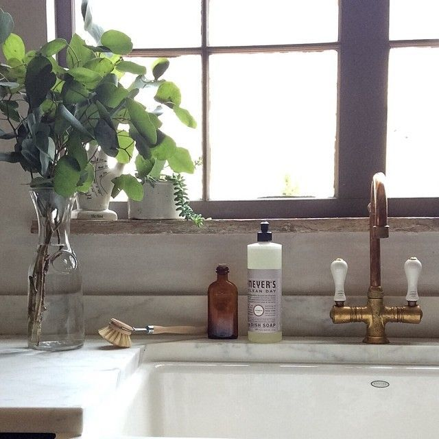 An elegant kitchen sink with a gold faucet and fixtures and an ...