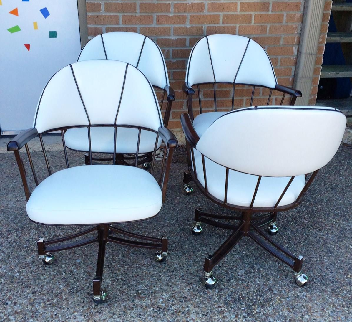 Set of four 1970s swivel rocking chairs with casters. New