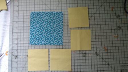 Você vai precisar de um dois tecidos, de preferência que sejam contrastantes.  Recorte um quadrado de 15cm e quatro quadrados de 9cm.   Se você quizer aumentar sempre leve em conta que a diferença entre o quadrado maior e os outros quadrados deve ser de 6cm.